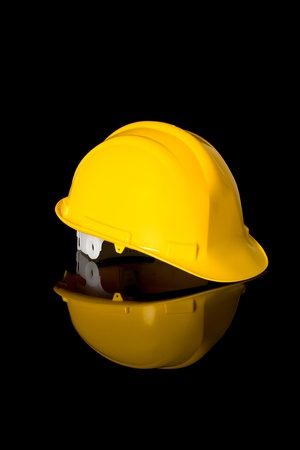 safety gear: yellow safety hard hat, right hand side angle shoot, studio shoot isolated on black with reflection Stock Photo