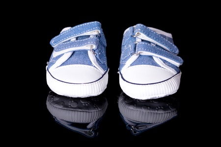 pair of new little blue baby shoes, newborn or pregnancy concept, studio shoot isolated on black with reflection photo
