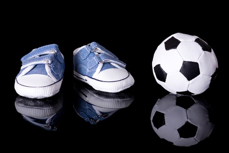 pair of small baby shoes next to football ball, footballer baby or baby footballer concept, studio shoot isolated on black with reflection photo