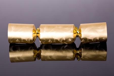 christmas cracker: traditional christmas golden cracker, studio shoot, reflection