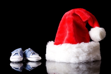 santa claus hat with pair of little baby shoes next to it, studio shoot isolated on black with reflection,  photo