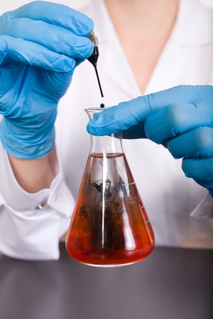 laboratory tests with test tube and small pipette filled with black liquid, water contamination, experiment