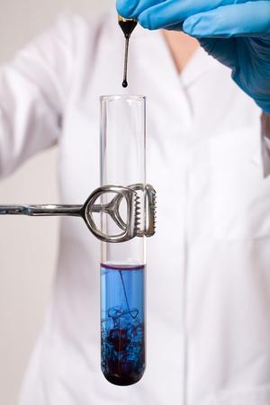 water contamination: asistente de laboratorio haciendo algunas pruebas de laboratorio, tubos de ensayo con el l�quido azul y uno negro con una pipeta, las pruebas, la contaminaci�n del agua