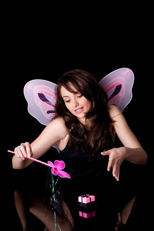 fairy with pink wings and magic wand doing some magic over small gift box, studio shoot isolated on black photo