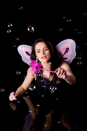 attractive adult fairy with pink wings and magic wand doing some magic with bubbles, studio shoot isolated on black photo