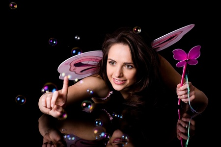 fairy with pink wings and magic wand trying to catch bubbles, studio shoot isolated on black