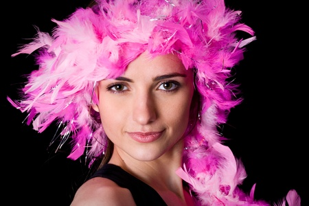black boa: closeup photo of beautiful woman face with pink feather boa covering her hair, studio shoot isolated on black background Stock Photo