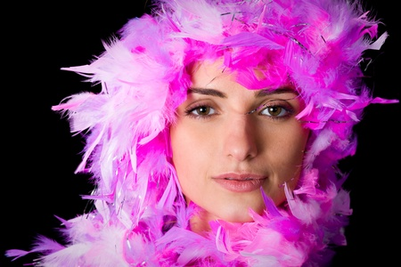 black boa: young woman beautiful face wrapped with pink, violet boa, studio shoot isolated on black background