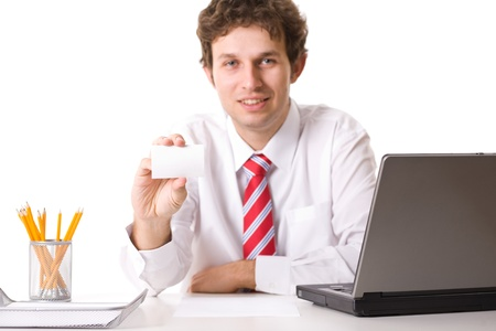 young businessman sits on his desk with laptop, pencils and paper tray and shows his empty, blank business card, studio shoot isolated on white photo
