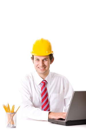 computer engineer: young happy engineer with yellow hard hat works on his laptop, studio shoot isolated on white Stock Photo