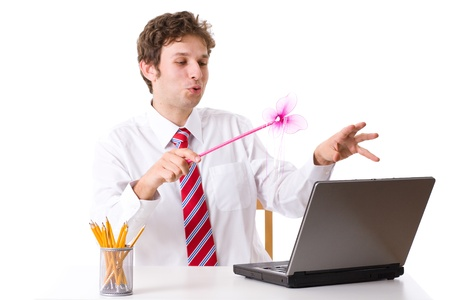 young businessman doing some magic over his laptop, uses pink magic wand, studio shoot isolated on white