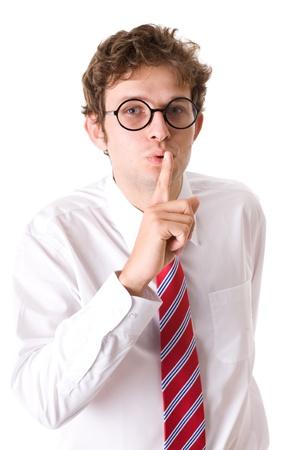 """guardar silencio: gesto joven empresario atractivo muestra 'silen por favor """", el dedo en los labios, lleva camisa, corbata roja y especificaciones, lanzamiento del estudio aislado en el fondo blanco Foto de archivo"""