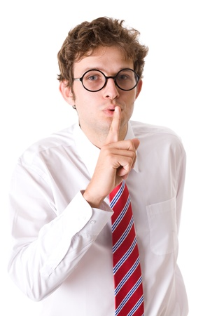 shh: young attractive businessman shows silen please gesture, finger on his lips, wears shirt, red tie and specs, studio shoot isolated on white background