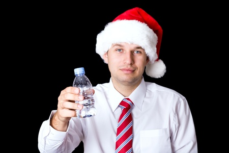 young tired and exhausted santa with bottle of water, studio shoot isolated on black Stock Photo - 11617521