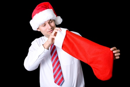 young attractive santa checks empty christmas sock, studio shoot isolated on black photo