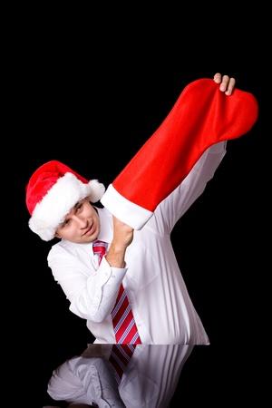 young attractive santa checks empty christmas sock, studio shoot isolated on black photo
