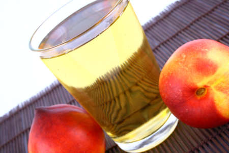 Glass of icetea and nectarine fruit - close-up Stock Photo