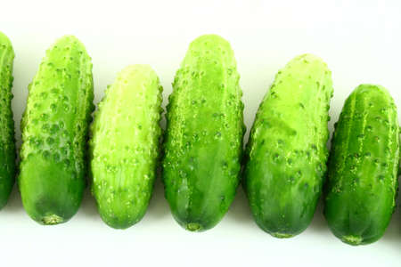 unsliced: A Cucumber progressively sliced on a white background