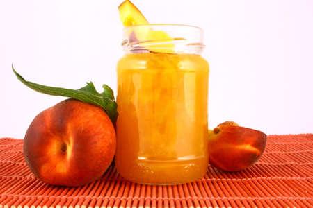 Peach jam on white background in jar