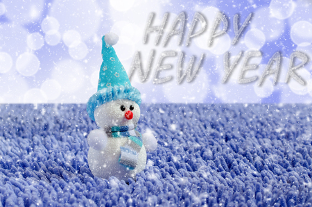 Toy Snowman with hat and scarf. Falling snow. Blue background Imagens