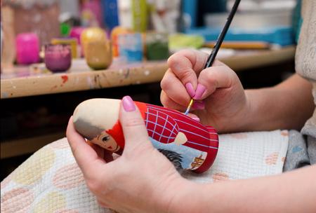 The artist draws a doll-matryoshka. Hand closeup. Photo