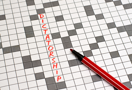 Dictatorship. Text in crossword. Red letters. Close-up
