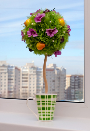 Artificial topiary. Handmade -  flowers with fruit. On the window.  The background multi - storey city house