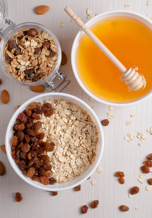 Healthy Breakfast. Oatmeal with raisins in white bowl. Almonds, honey on white  table background. Flat top view Stock Photo
