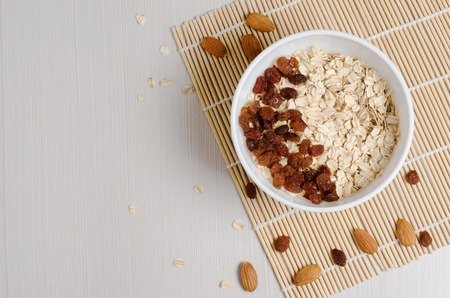 Oatmeal with raisins on the tablecloth from bamboo. Space for text