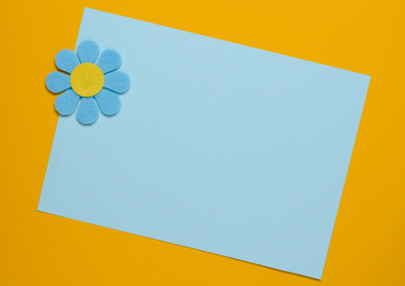 Blue flower made of felt on a blue and orange background. Greeting card. Space for text Standard-Bild