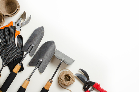Garden tools and gloves on a white background. Space for text. Flat top view