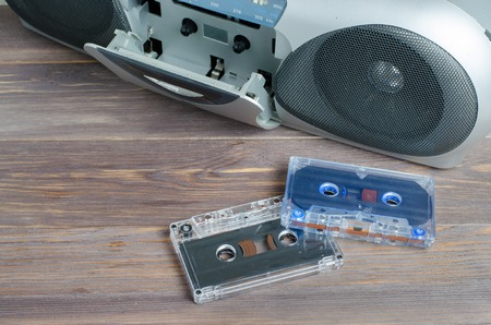 Two audio cassettes and a tape recorder on wooden background Stockfoto