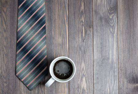 Herrenkrawatte und Kaffee in einer weißen Tasse auf Holzuntergrund. Flache Draufsicht