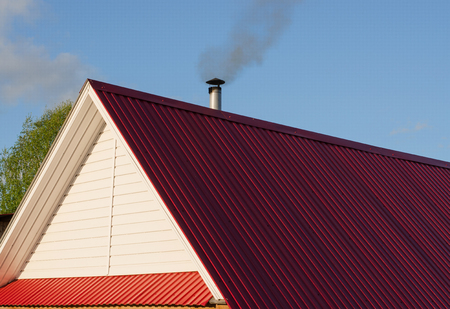 Tiled roof top with chimney with blue cloudy sky in background. Smoke raising from a chimney. Summer, noon. Stock Photo