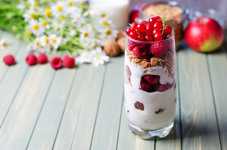 Healthy breakfast. Dessert in a glass-yogurt, oatmeal, raspberry, red currant. Walnuts, red apples, flowers, milk. Wooden background. Side view. Copy space Imagens - 122093481