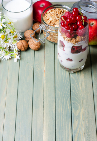 Healthy breakfast. Dessert in a glass-yogurt, oatmeal, raspberry, red currant. Walnuts, red apples, flowers, milk. Wooden background. Side view. Copy space. Vertical photo