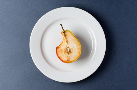 Stale old pear on a round white plate. Bite mark. Dark background