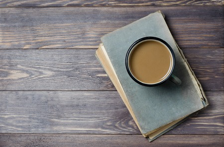 An old book with a torn cover. Coffee with milk. Wooden background. Flat top view Stock fotó