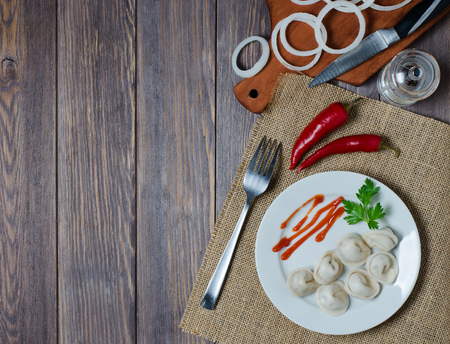 Traditional Russian dumplings, ravioli, pelmeni on a white plate with red sauce and parsley. Dark wooden background.