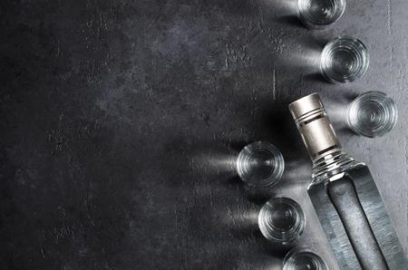 Bottle of vodka. Vodka in glass glasses. Dark black background. Copy space