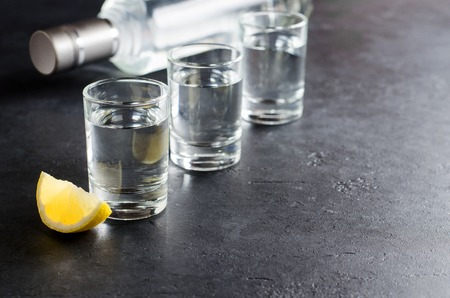 Three glasses, a bottle of vodka, a piece of lemon on a dark background. Copy space