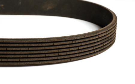 Old worn rubber alternator belt with cracks. Close up. White background Stock Photo