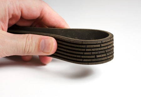 The old worn out rubber alternator belt in mens hand. The concept of car maintenance Stock Photo