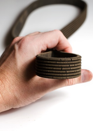The old worn out rubber alternator belt in men's hand. The concept of car maintenance. Vertical photo Stok Fotoğraf