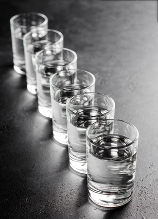 Glasses of vodka are in a row on dark background. Selective focus. Space for text. Vertical photo