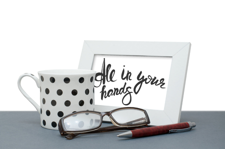 All in your hands. Handwritten inscription in the frame. Coffee Cup, glasses, pen. Close-up