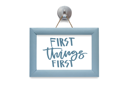 First things first. Modern calligraphy. Motivational quote. Blue photo frame. Isolated on white Imagens - 122529828