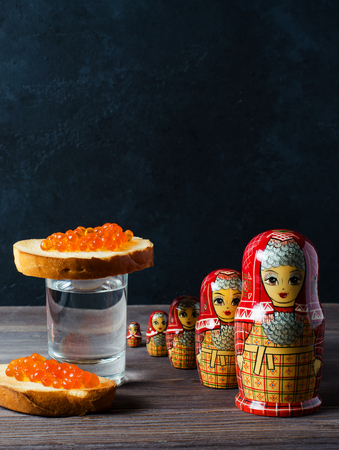 Sandwiches with red caviar of salmon fish. A glass of vodka, matryoshka. The concept of Russian tradition. Copy space. Vertical photo