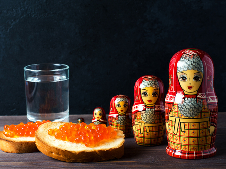 Sandwiches with red caviar of salmon fish. A glass of vodka, matryoshka. The concept of Russian tradition. Copy space