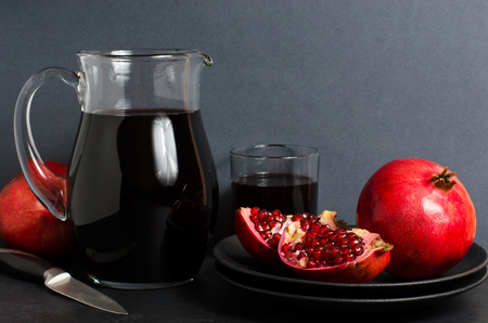 Pomegranate, pomegranate juice in a glass Cup. Dark background. Side view. Copy space Banco de Imagens
